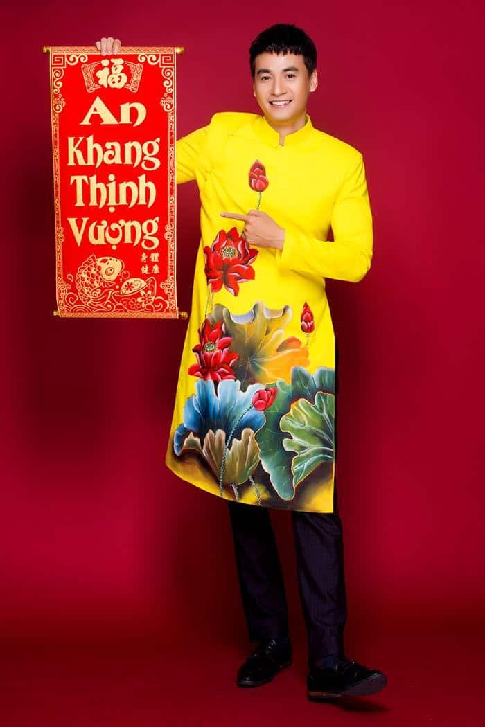 Áo dài nam vàng nổi bật với hoa sen đỏ